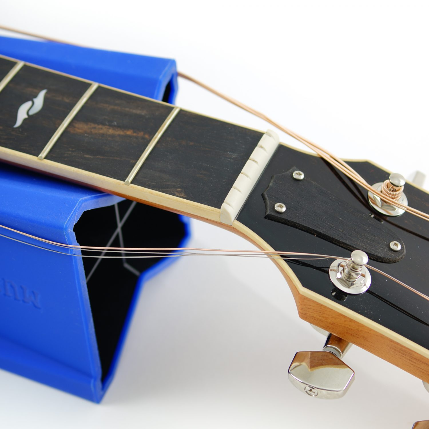 Cradle Cube holding back acoustic guitar strings